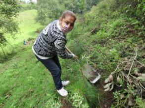 Woman from N. Romero community planting a tree