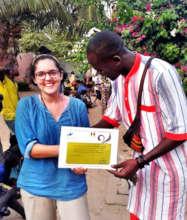 Abdou giving Simone a certificate of appreciation
