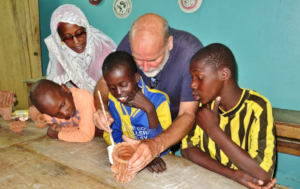 Christoph and Aida guide children making potery