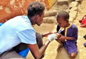 Elhage gently examines a child's sore knee