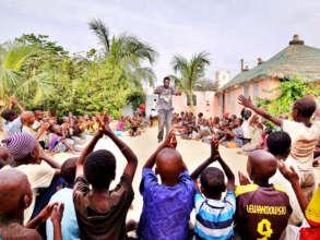 Teacher Abdou leading singsong in MDG center