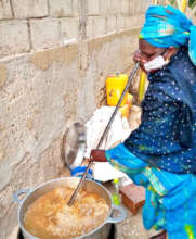 "A neighborhood ""Godmother"" preparing the meal"