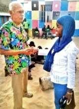 Chuck greets Maison de la Gare nurse Awa Diallo
