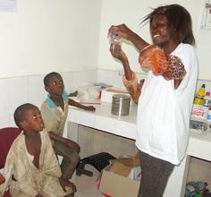 Nurse Binta Coly with two adoring patients