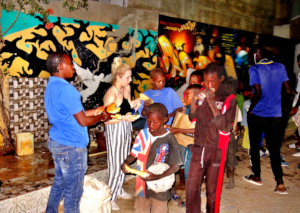 Distributing food to talibes with volunteer Alicia