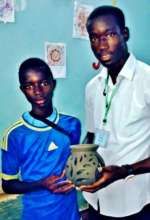 A volunteer and his student with pottery creation