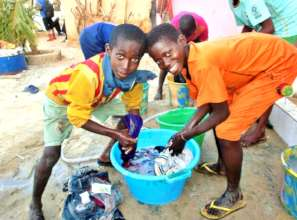 Talibe children enthusiastically washing clothes
