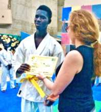 Issa receiving his yellow belt from Sonia LeRoy