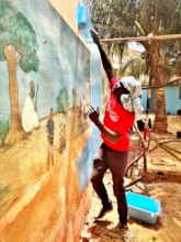 Abdou painting wall, preserving a beautiful mural