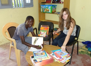 Rowan labeling books in MDG library with Kalidou
