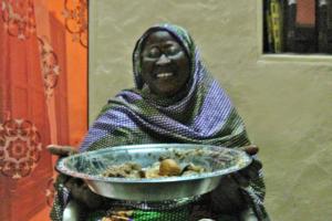 Sam's host mother serving a lamb stew