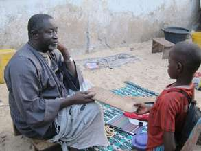 Marabout Seck instructing a child