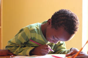 Child intent on coloring in MDG library