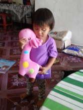 Maira embracing her favorite pink chou chou giraff