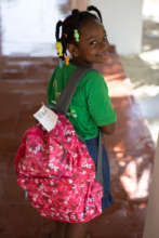 Elidania shows off her backpack of school supplies