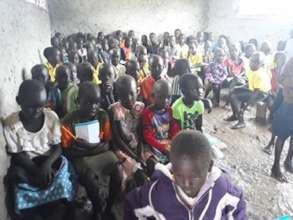 Students  in a classroom affected by water and mud