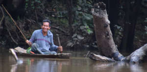 9. Smiling man fishing from dugout canoe