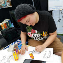 Tessa and the Draw a Toucan game at CACE booth