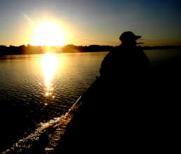 Bora man in boat at sunset