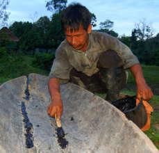 Bora man caulking canoe with copal resin