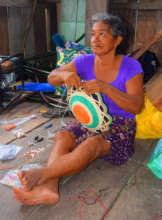 Romelia putting beads on basket