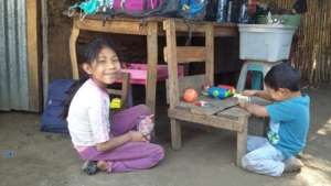 Carmeli and her little brother outside their home