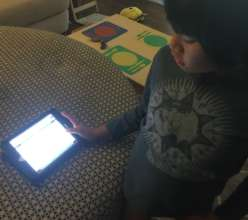 Aiden using his iPad mini at home