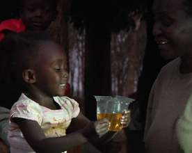 Child drinking ORS from Kit Yamoyo measuring cup
