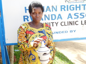 A beneficiary proudly displaying a basket she made
