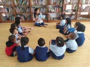 Ms. Rusti reading a book for the students