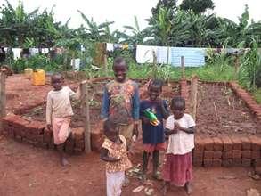 Children in front of the raised garden beds