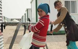 Girls collect water in Zatari camp