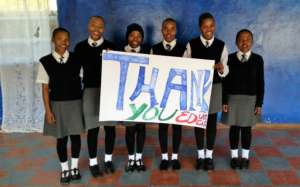 A group of smiling girls with a message of thanks.