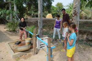 Mother shows Thiessens how to use pull pump well.