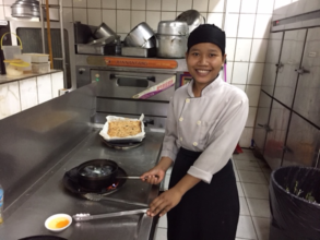 Somnang cooking at her job.