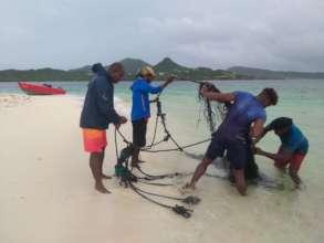 Removing a fish trap. Photo: Davon Baker