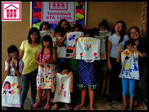 Girls show their hand-painted canvas bags