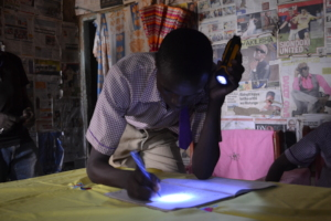Boniface using his flashlight for homework