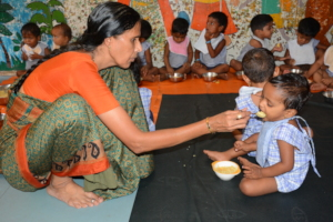 Teacher feeding nutritious meal to a creche child
