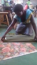 A woman making School Uniform at Amwonya
