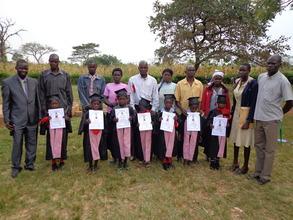 Children display their graduation certificates