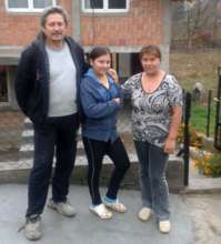 Sanja with her parents in front of the new house