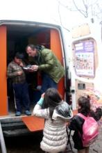 Ilir helps a boy choose his book
