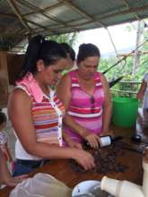 Maria y Isabel cracking the toasted chocolate