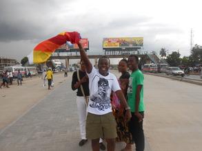 Abdallah waving a Rainbow flag