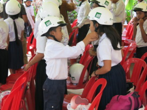 Students help each other put on their new helmets.