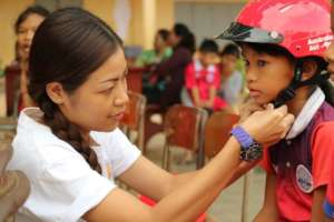A YARS team member helps a student wear a helmet.