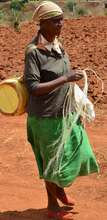 Woman weaving a rope on her way to fetch water