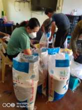 Volunteers pack rice packets for families