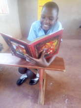 Ritah reading a donated book by a friend